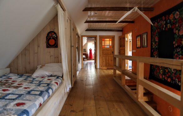Teise korruse katuseviilu all olevat magamis- kohta kaunistab pereema maalitud seinakell.